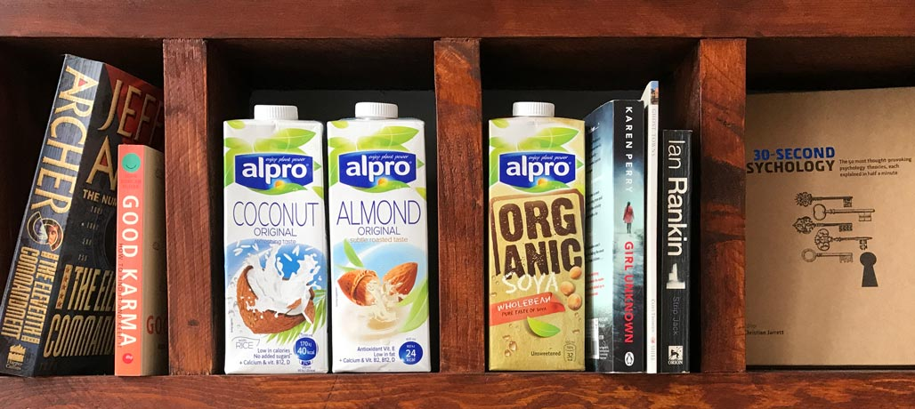 alpro coconut and almond milk on book shelf
